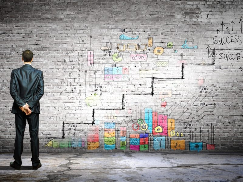 Businessman examining wall with success graffiti