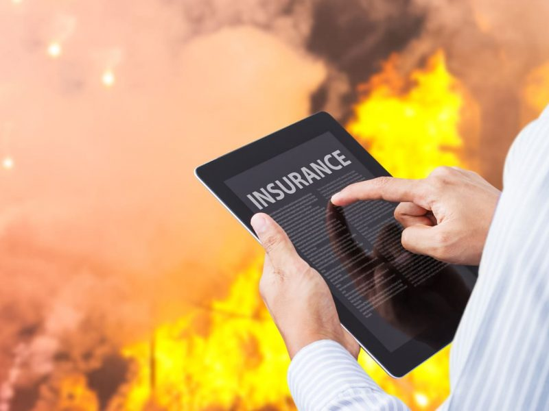 Man pointing at insurance wording on tablet with fire background