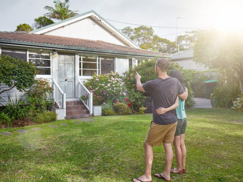 Happy mixed-race couple standing in front of house.